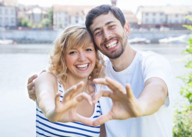 Paare im äußeren darstellenden Herzen der Liebe mit den Fingern lizenzfreie stockfotos