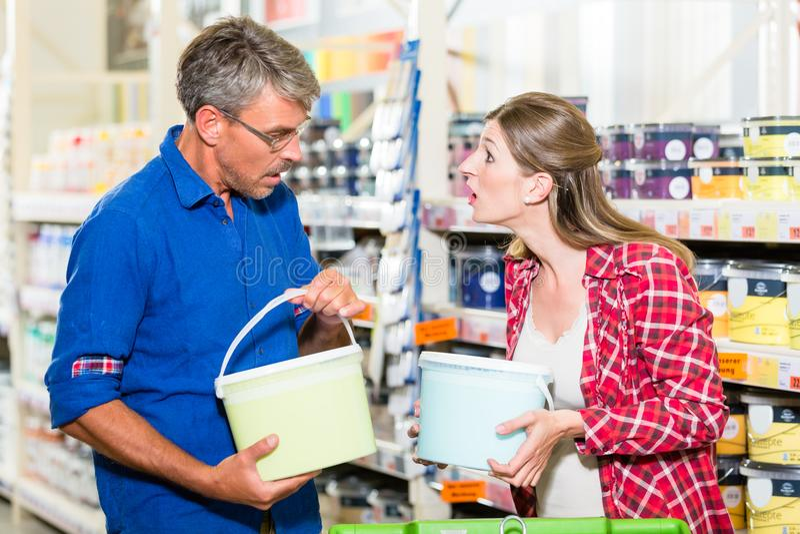 Paare im Baumarkt, der über Farbe der Farbe für die Erneuerung argumentiert stockfotografie