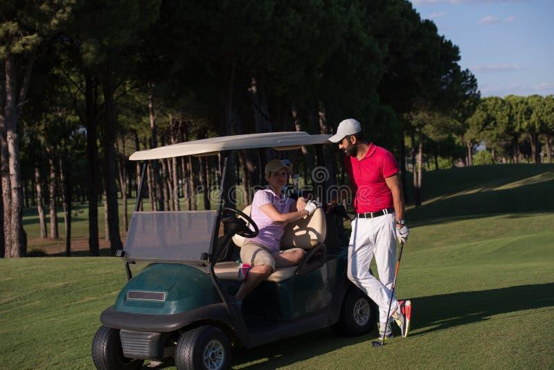 Paare im Buggy auf Golfplatz stockfoto