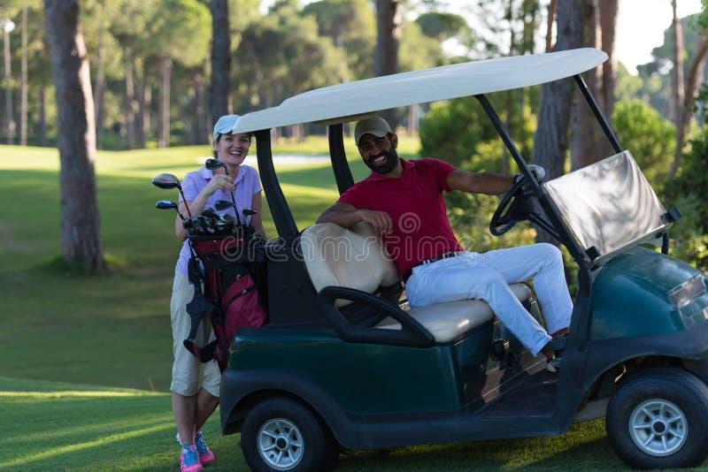 Paare im Buggy auf Golfplatz lizenzfreies stockbild