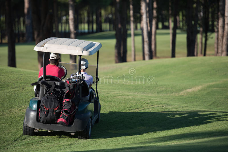 Paare im Buggy auf Golfplatz stockfotos