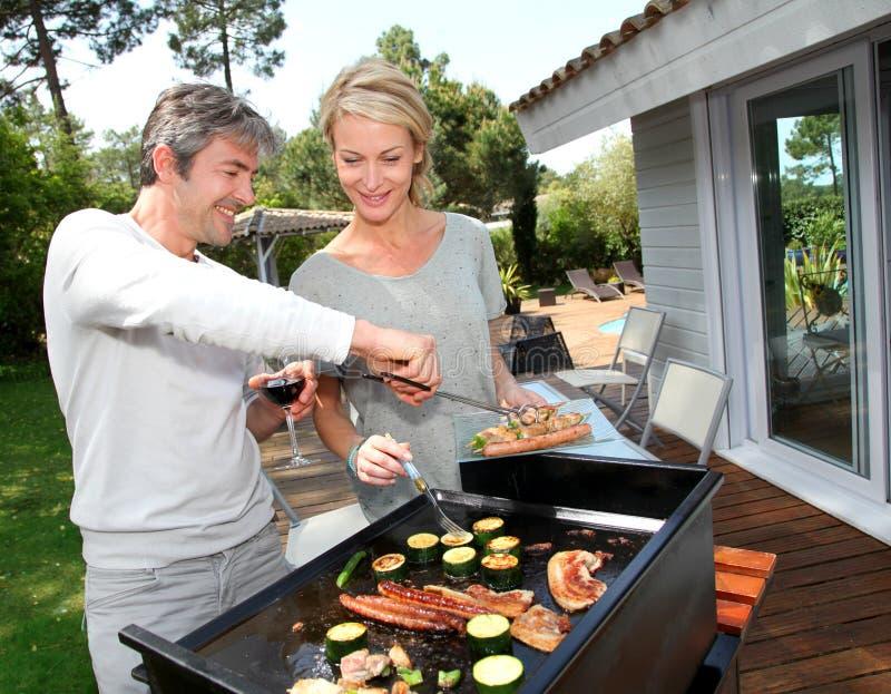 Paare im Garten, der Grill macht lizenzfreie stockbilder