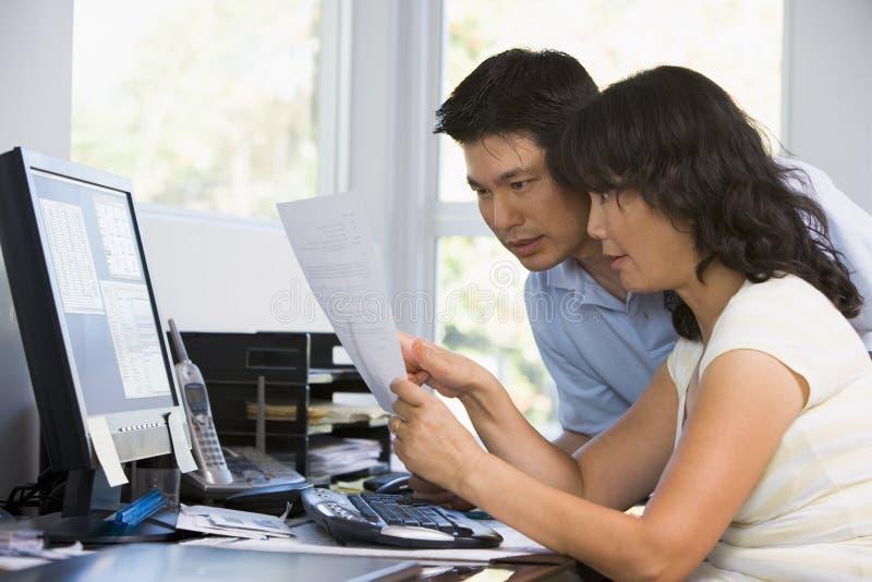 Paare im Innenministerium mit Computer und Schreibarbeit lizenzfreie stockbilder
