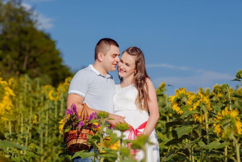 Paare im Liebesehemann und -frau, die draußen in Sonnenblumenfeld gehen lizenzfreie stockfotos