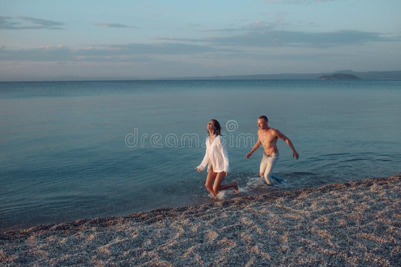 Paare im Liebeslauf auf See- oder Ozeanstrand im Wasserspritzen Getrennt auf Schwarzem Frau trägt männliches Hemd und Betrieb im  lizenzfreies stockfoto