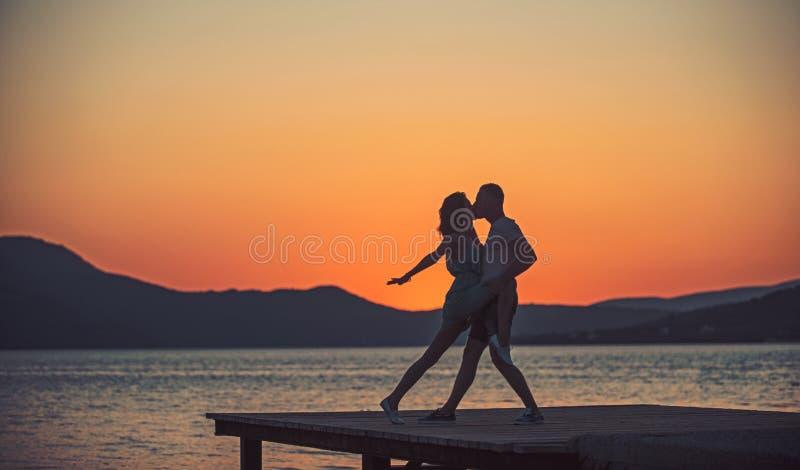 Paare im Liebestanz auf Sonnenaufgangstrand Paare im Liebestanz in der Dämmerung auf Pier stockfoto