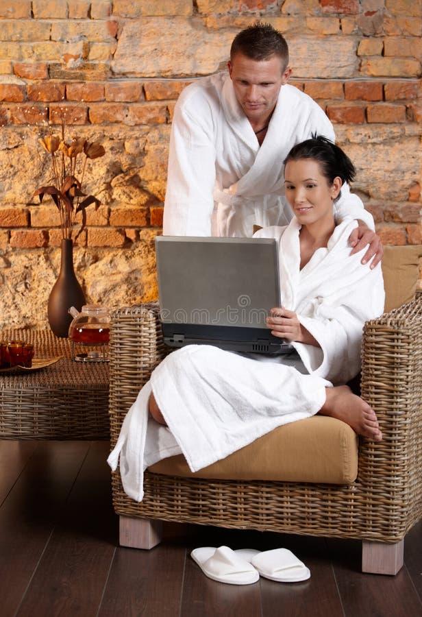 Paare im Wellness unter Verwendung des Laptops lizenzfreies stockfoto