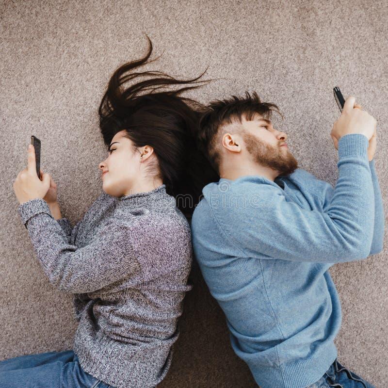 Paare im Wohnzimmer unter Verwendung der intelligenten Telefone stockfotografie