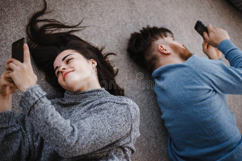 Paare im Wohnzimmer unter Verwendung der intelligenten Telefone lizenzfreie stockfotos