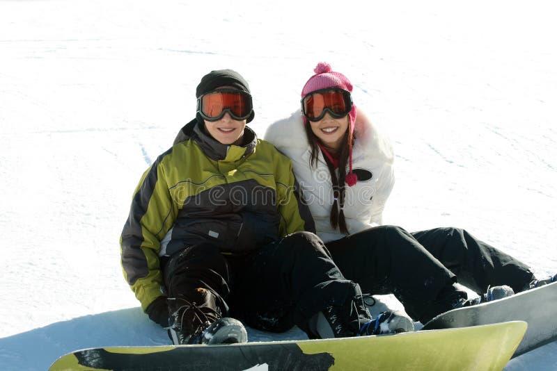 Paare jugendlich Snowboarders lizenzfreie stockfotos
