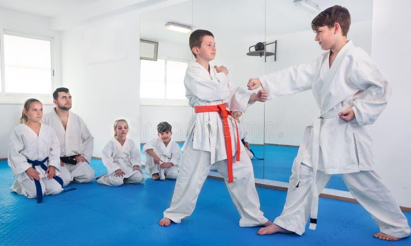 Paare Jungen, die neue Karatebewegungen üben stockfotografie