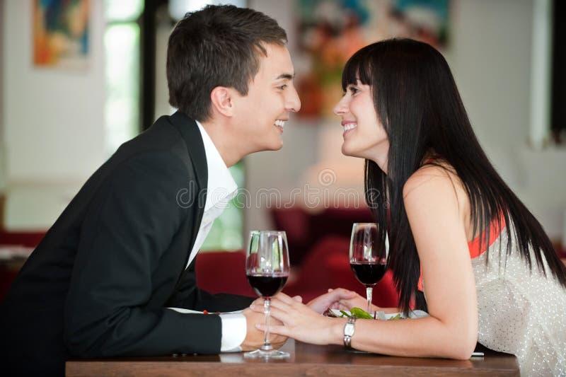 Paare küssen über Mahlzeit lizenzfreie stockfotos