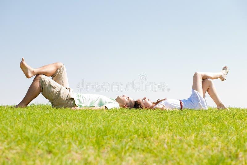 Paare legen sich auf Gras hin stockfotografie