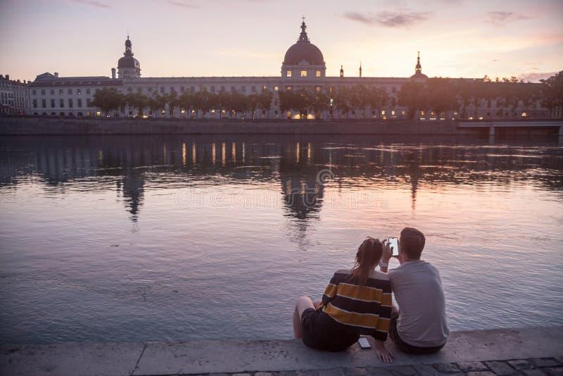 Paare, Liebhaber, ein smarthone auf dem Riverbank der Rhônes, auf dem Quais De Rhône betrachtend und stellen Hotel Dieu gegenüber stockbild