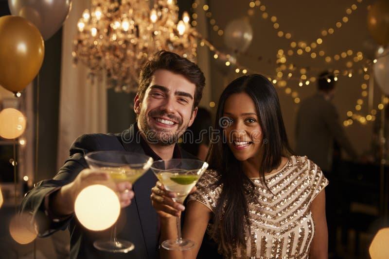 Paare machen Toast an der Kamera, während sie an der Partei feiern stockbilder