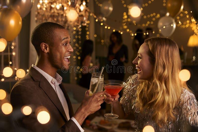 Paare machen Toast, während sie an der Partei zusammen feiern lizenzfreie stockbilder