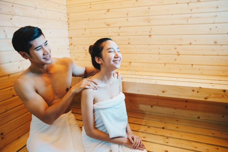 Paare, Mann und Frau waren, trinkend sitzend und Wein in der Sauna stockfotografie