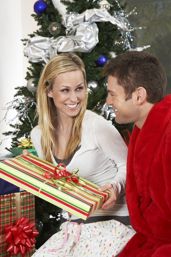 Paare mit anwesendem Sitzen durch Weihnachtsbaum lizenzfreie stockbilder