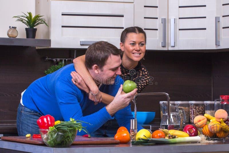 Paare mit Apple in der Küche lizenzfreie stockfotografie