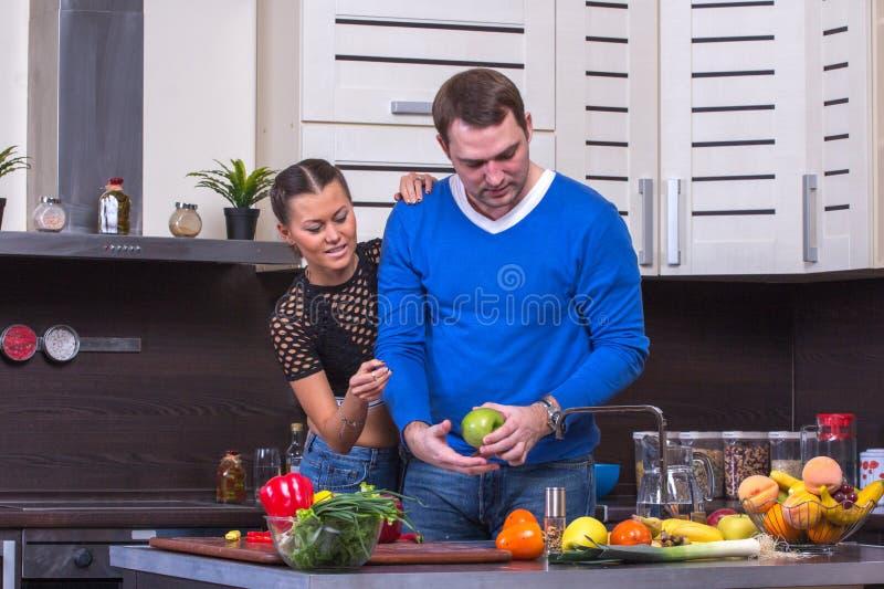 Paare mit Apple in der Küche lizenzfreie stockfotos