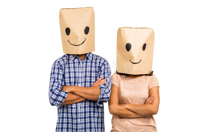 Paare mit Arme gekreuzten tragenden smileypapiertüten lizenzfreie stockfotografie