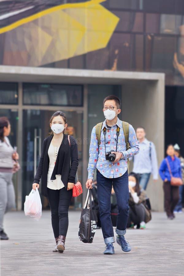 Paare mit Atemschutz im Gewerbegebiet, Peking, China stockfoto