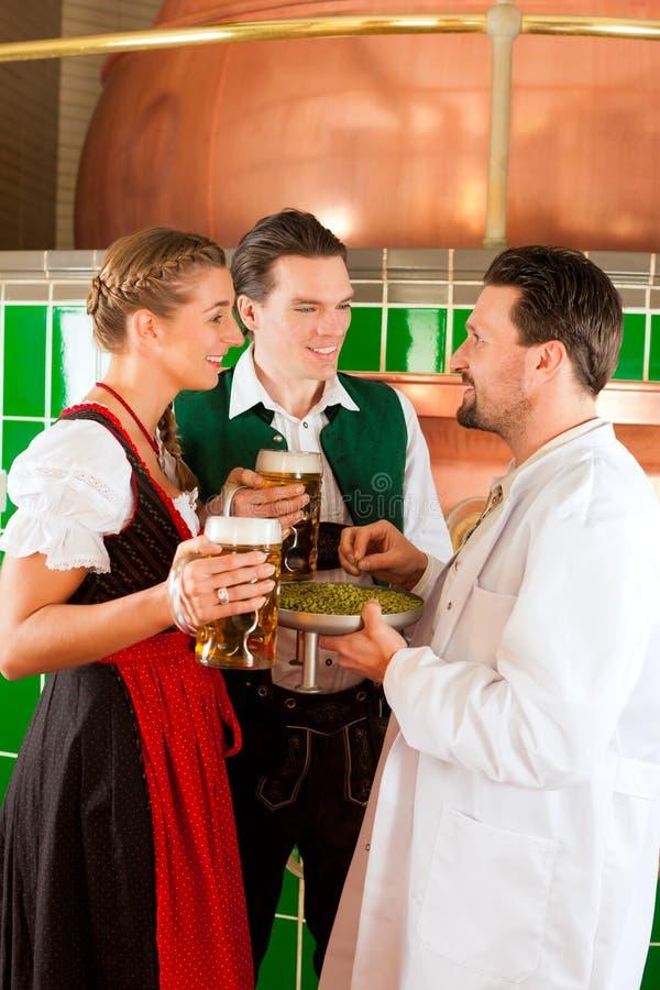 Paare mit Bier und ihrem Brauer in der Brauerei lizenzfreies stockfoto