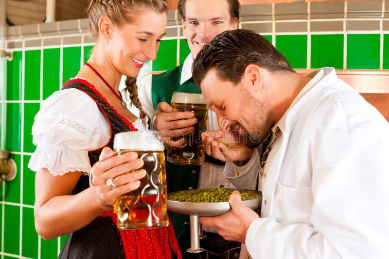 Paare mit Bier und ihrem Brauer in der Brauerei lizenzfreie stockbilder