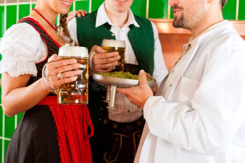 Paare mit Bier und ihrem Brauer in der Brauerei lizenzfreie stockfotos