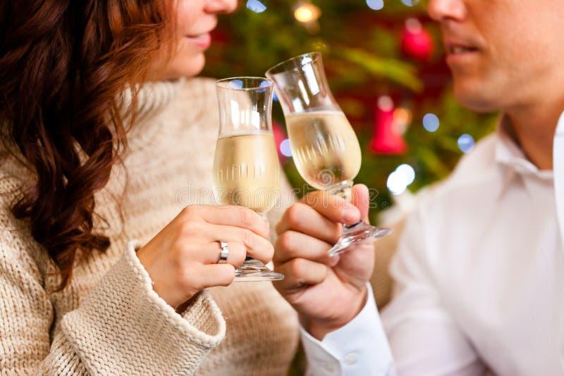 Paare mit Champagner auf Weihnachtsabend stockfotos