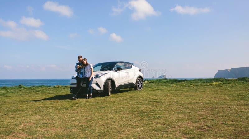 Paare mit dem Auto, das beweglich schaut lizenzfreies stockfoto