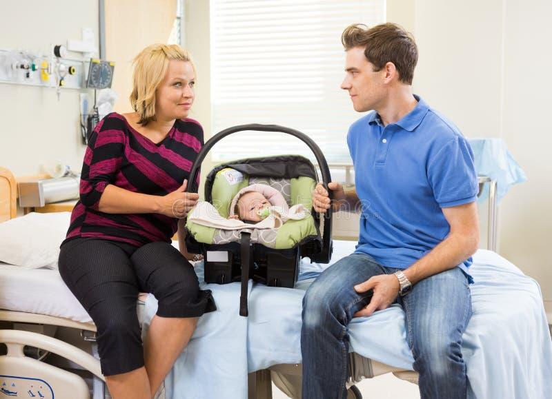 Paare mit dem Baby, das einander auf Krankenhaus betrachtet lizenzfreies stockbild