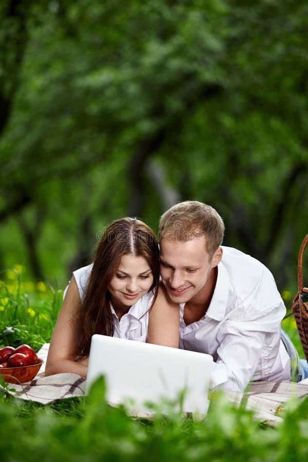Paare mit dem Laptop im Park lizenzfreie stockfotografie