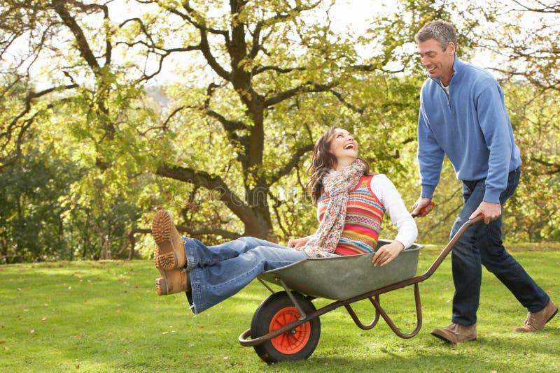 Paare mit dem Mann, der Frauen-Fahrt in der Schubkarre gibt lizenzfreie stockfotos