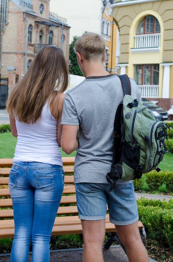 Paare mit dem Rucksack, der Karte betrachtet stockbilder