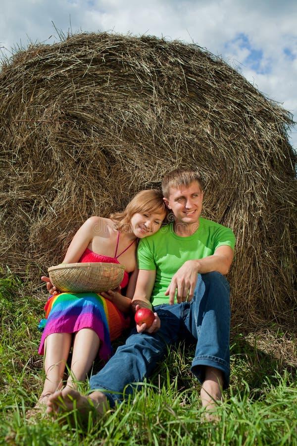 Paare mit den Äpfeln, die auf dem Gras sitzen, heuen lizenzfreie stockfotos