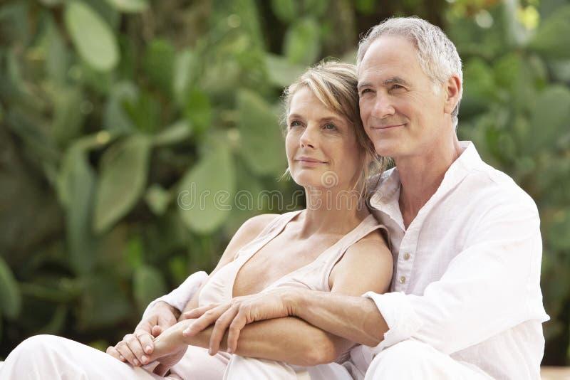 Paare mit den Armen um die Entspannung im Garten stockfotos