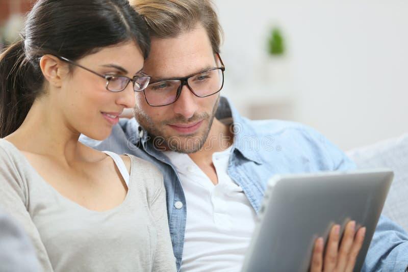 Paare mit den Brillen angeschlossen auf Tablette lizenzfreie stockfotos