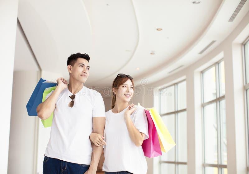 Paare mit den Einkaufstaschen, die in Mall gehen stockfoto