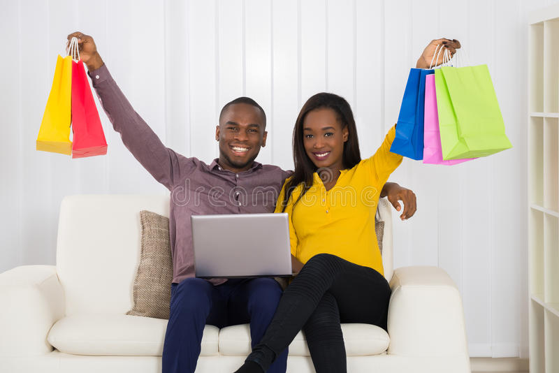 Paare mit den Einkaufstaschen und Laptop, die auf Sofa sitzen lizenzfreies stockfoto