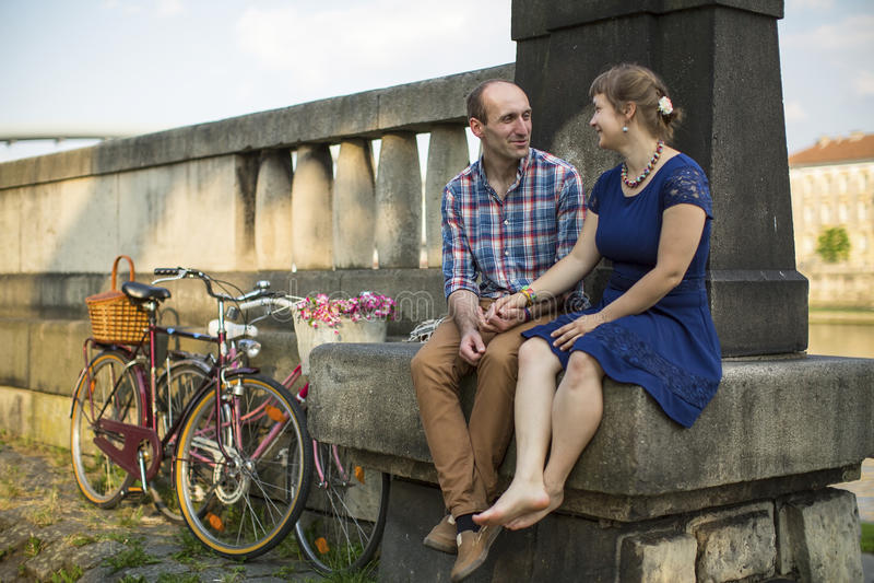 Paare mit den Fahrrädern, die auf einem Steindamm sitzen Liebe lizenzfreie stockbilder