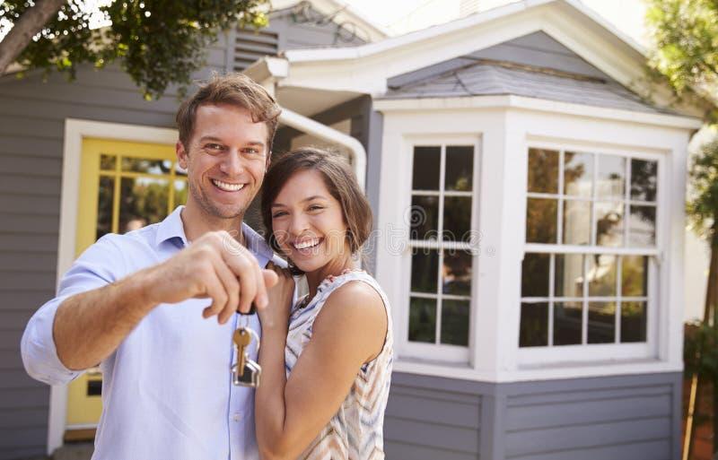 Paare mit den Schlüsseln, die äußeres neues Haus stehen