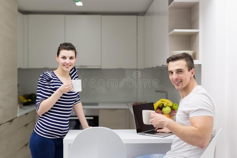 Paare mit der Laptop-Computer, die Morgen genießt stockfotografie