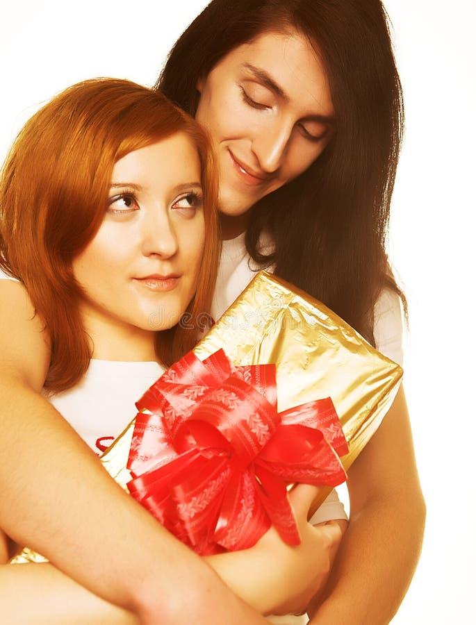 Paare mit einem Geschenk über einem weißen Hintergrund stockbilder