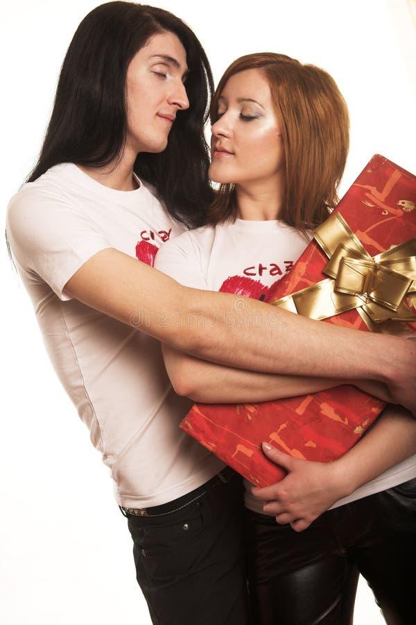 Paare mit einem Geschenk über einem weißen Hintergrund lizenzfreie stockfotografie