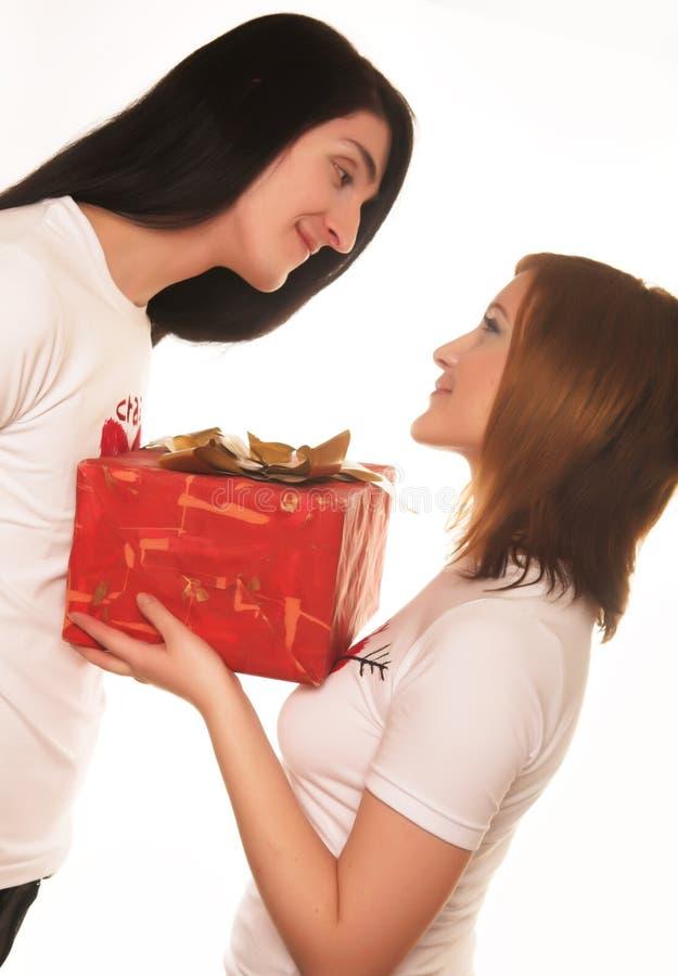 Paare mit einem Geschenk über einem weißen Hintergrund stockfotografie