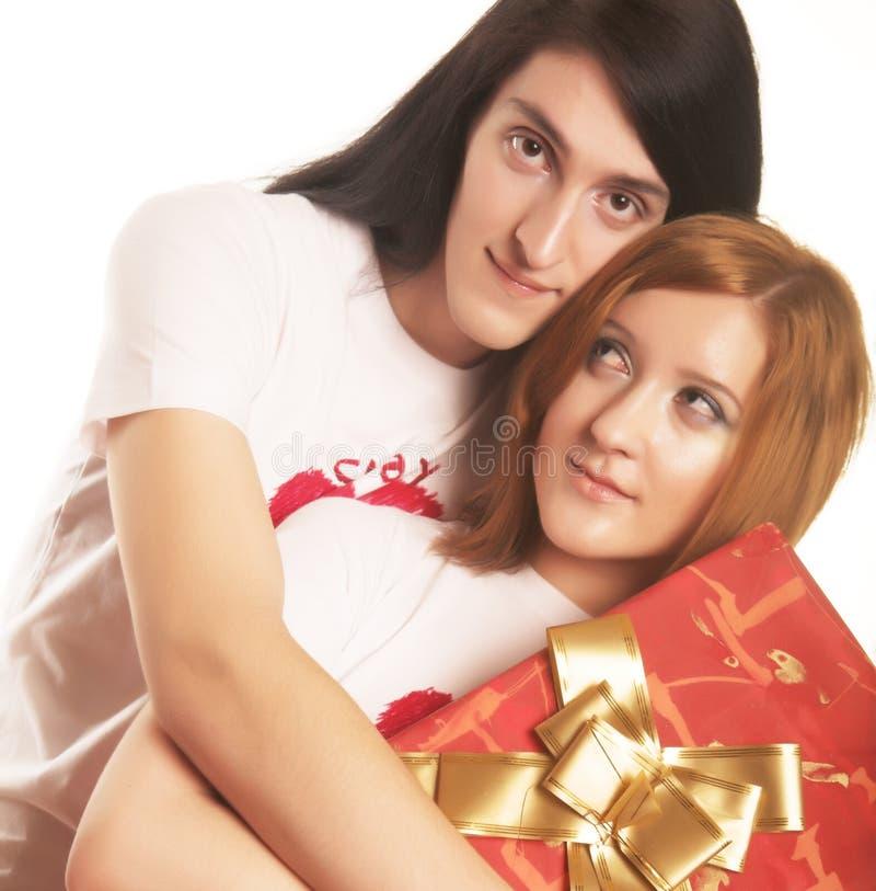 Paare mit einem Geschenk über einem weißen Hintergrund stockbild
