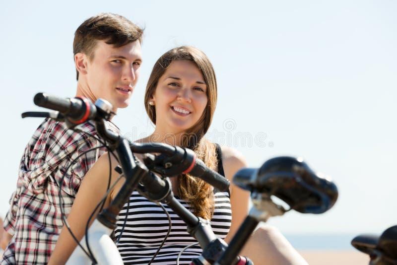 Paare mit Fahrrädern auf Strand stockbilder