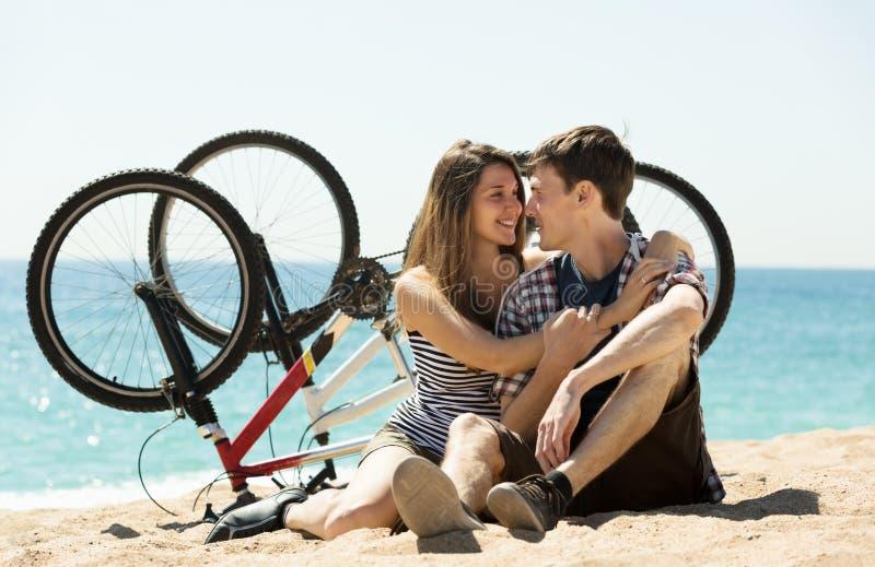 Paare mit Fahrrädern auf Strand lizenzfreies stockbild