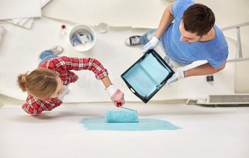 Paare mit Farbenrollen-Malereiwand zu Hause lizenzfreie stockbilder